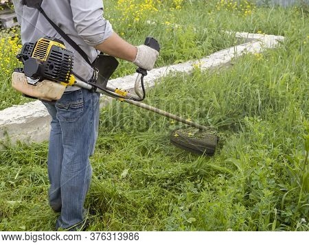 A Man Mows The Thick Tall Grass With A Gasoline Trimmer. The Lawn Mower's Work