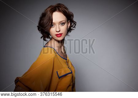 Frontal Portrait Of A Young Short-haired Woman Looking At The Camera, With Make-up And Red Lips, Ove