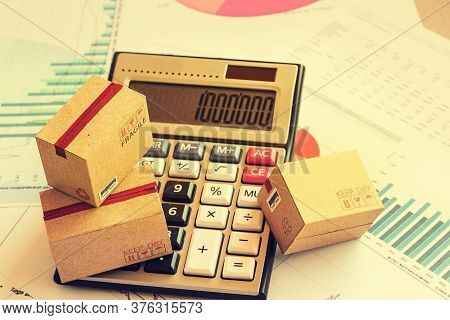 Closeup Three Cardboard Boxes Packing The Product And Calculator On Technical Chart Of Financial Exp