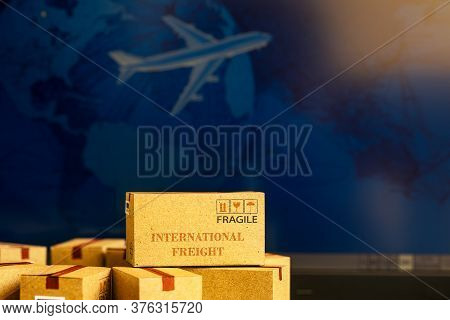 Small Paper Boxes On Notebook With A Plane Flies Behind. An Ideas About Transportation, Internationa