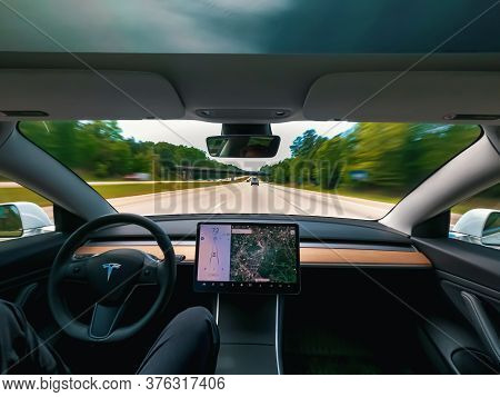 Raleigh, Nc Usa, May 09, 2020: Person Driving A New Tesla Model 3 On Autopilot