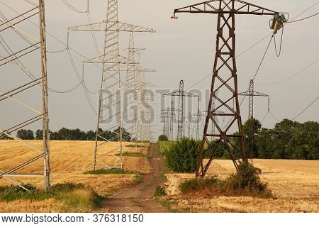 Dirt Country Road Between Fields Of Ripe Dry Wheat On A Background Of Metal Pylons Electrical Wires