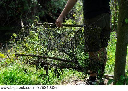 Male Fisherman Holds A Fishing Net. Poaching Fishing