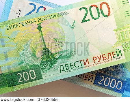 Russian Banknote 200 Rubles Lies On The Banknote 2000 Rubles. The Bill Depicts A Monument To The Scu