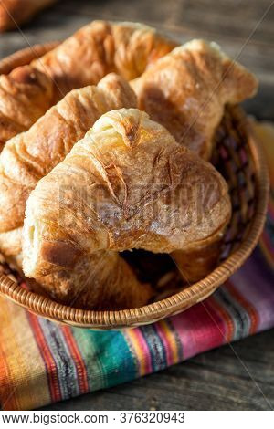Warm croissant, served in a wicker serving plate with a striped napkin, over old wood table. Retro style processing and vignette
