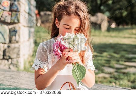 Portrait Of Cute, Little Girl Smelling Flowers In Her Hands