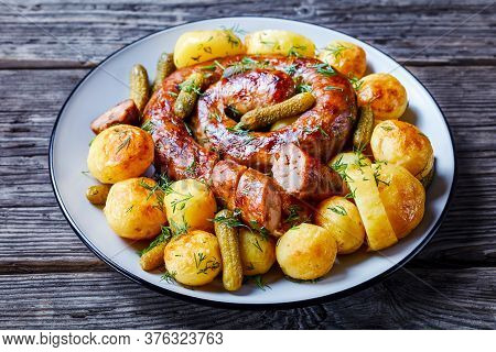 Old Fashioned German Dish: Young Potato Boiled And Fried, Served With Pork Sausage And Pickled Cucum