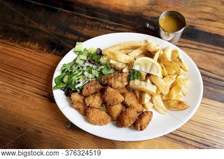Home Made Scampi And Chips Served With Mixed Vegetables Salad And Lemon On Top, English Traditional