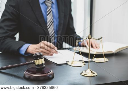 Scales Of Justice And Judges Gavel Standing In Front Of The Male Lawyer Is Providing Service To Cons