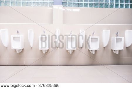 Men's Toilet Public With White Porcelain Urinals Stall, Modern  Clean Bathroom For A Pee.