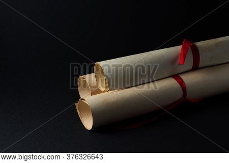 Vintage Scrolls On A Black Background. Three Scrolls Lie On Top Of Each Other. Scrolls Wrapped In Re