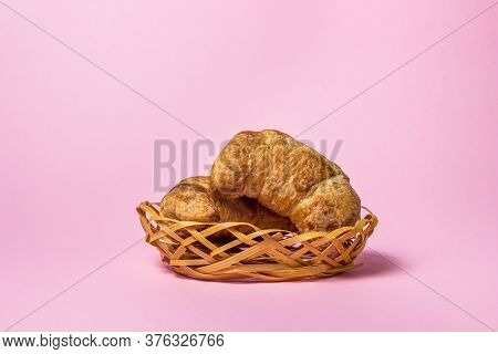 Croissants On A Pink Background. Two Croissants Lie In A Small Wicker Basket