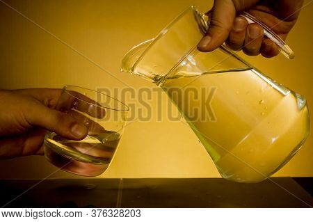 Elegant Shot Of Two Hands Preparing To Pour Some Water From A Pitcher Into A Glass On A Dark Backgro