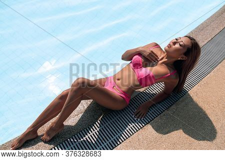 Gorgeous Asian Woman In A Pink Bikini Lying By The Crystal Clear Pool During Her Awesome Vacation In