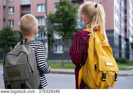 Back View Brother And Sister Going School After Pandemic Over. Kids Wearing Mask And Backpacks Prote