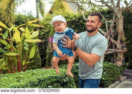 Bearded Man Carrying Young Boy. Smiling Dad Holding Son. Joyful Father Playing With His Little Kid.