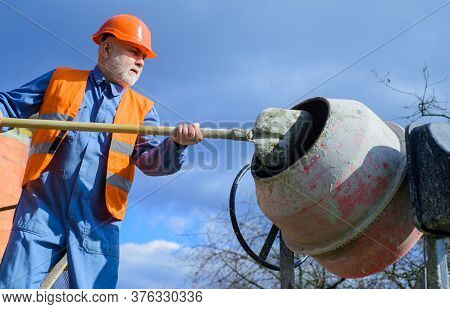 Construction Worker With Spade In Hand. Builder Works With Concrete Mixer. Concrete Mixer Prepares C