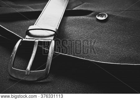 Closeup Of A Leather Belt With Metalic Buckle Near A Suit Button On A Business Coat