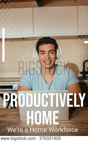 Smiling Bi-racial Man Listening Music In Headphones And Using Laptop Near Productively Home, Were A