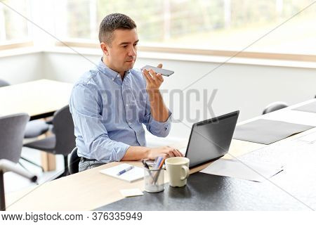 remote job, technology and business concept - middle-aged man with laptop computer calling on smartphone or using voice command recorder at home office