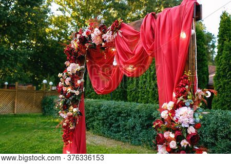 Wedding Ceremony, Wedding Arch, Red Wedding Arch Of Flowers And Greenery Stands On The Green Grass I