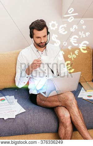 Teleworker In Shirt And Panties Drinking Coffee While Using Headset And Laptop On Couch, Currency Si