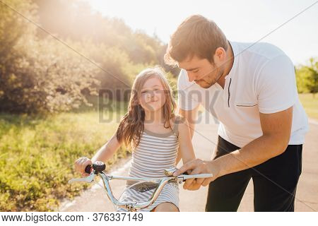 Front View, Little Girl Learning Ride Bicycle With Father. Young Father Teaching His Daughter To Rid