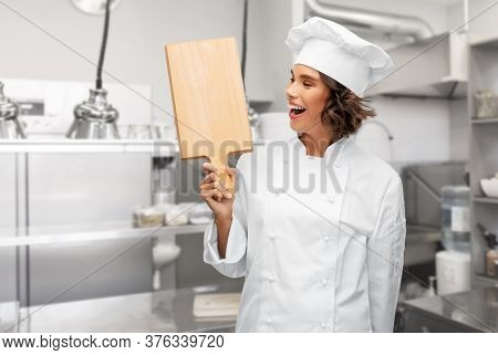 cooking, culinary and people concept - happy smiling female chef in toque with wooden cutting board over restaurant kitchen background