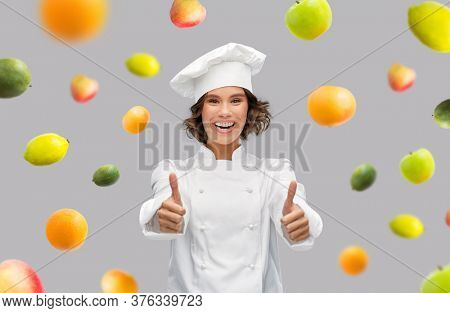 food cooking, gesture and people concept - happy smiling female chef in toque showing thumbs up over fruits on grey background