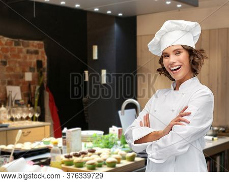 cooking, culinary and people concept - happy smiling female chef in toque with crossed arms over restaurant kitchen background