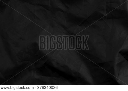 Abstract Black Synthetic Material With Wrinkles And Wrinkled Folds. Old Wrapping Dusty Cloth. Crumpl
