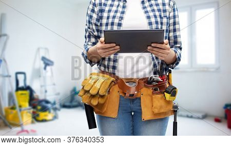 repair, construction and building concept - close up of woman or builder with tablet pc computer working tools on belt over utility room background