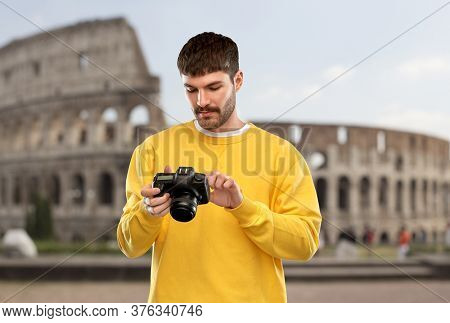 travel, tourism and photography concept - young man or photographer in yellow sweatshirt with digital camera over coliseum in rome, italy background