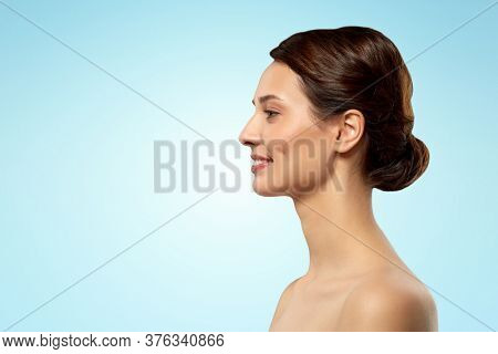 beauty, bodycare and people concept - profile of beautiful young woman with bare shoulders over blue background