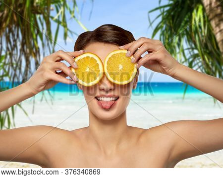 beauty, skin care and detox concept - beautiful woman making eye mask of orange slices and showing her tongue over tropical beach background in french polynesia