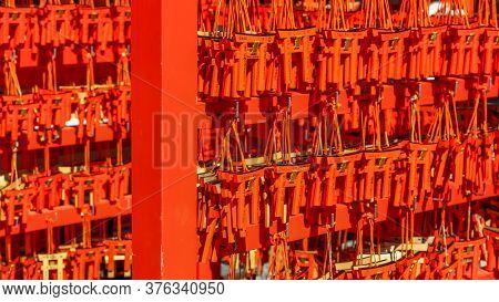 Kyoto, Japan - August 8, 2019. Many small red torii gates with prayers left by devotees at famous Fushimi Inari-Taisha Shinto Shrine in Kyoto, Japan