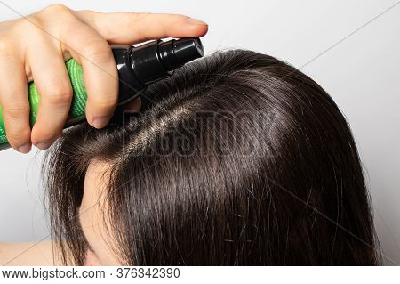 The Girl Puts On Her Hair A Tonic Of Hydrolyte From A Bottle. Hair Care At Home.