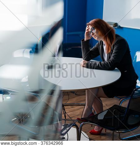 Tired Red-haired Business Woman In Glasses And A Suit Alone In An Empty Conference Room. An Office W