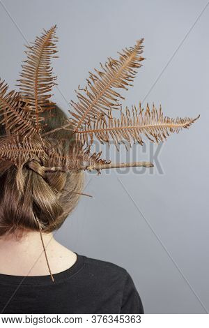 Rear View Portrait Of Brunette Girl With Crown Of Fern In Her Hair, Gray Background. Stylish Hairsty