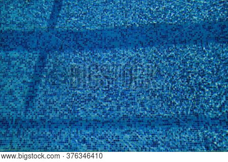 Swimming Pool Bottom Caustics Ripple And Flow With Waves Background. Surface Of Blue Swimming Pool,