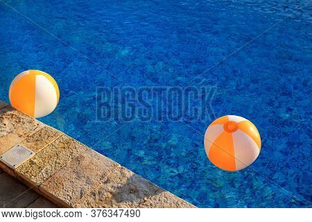 Two Rubber Air Yellow White Inflatable Balls And Toy For Swimming Pool In Transparent Blue Water. Mu
