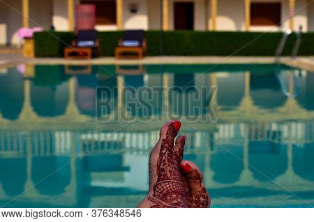 Newly Married Woman With Henna Feet In Front Of A Swimming Pool On Her Honeymoon In A Resort In Jais
