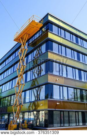 Modern Building Facade Repair Using A High Scissor Lift With A Platform