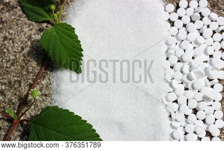 The Picture Shows A Candy Leaf, Sugar And Sweetener On A Stone Floor