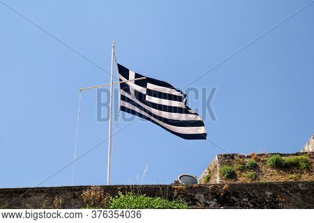 Close Up Of Blue And White Greek Flag On Flagpole Flying In The Wind. Torn Greek National Flag On Ol