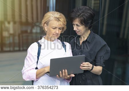 Two Mature Adult Senior Beautiful Women Looking At Laptop Computer Outdoors Business Centre. Ladies,