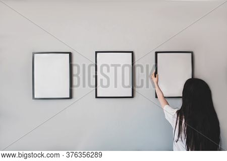 Girl Hangs A Frame On The Wall. Empty Place For Your Photo, Picture, Gratitude Letter, Design Or Log