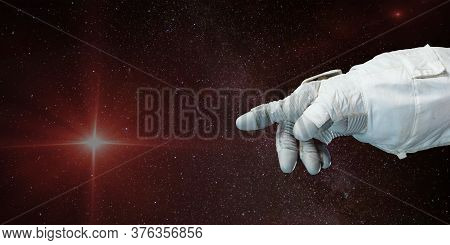 Astronaut Hand Pointing Toward The Star With Background Of Deep Space. Elements Of This Image Furnis