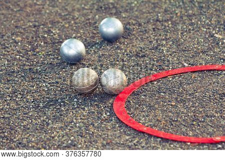 Boccia Balls On Ground With Red Aim Ring At Match. Fun Leisure Time Activity With Silver Boule Ball