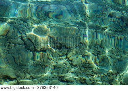 Top View Of Blue, Green And Turquoise Colors Of Water, Surface Of Sea On Rocks And Bottom. Reflectio